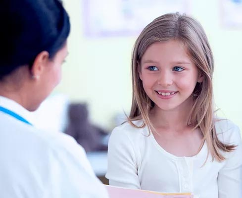 Young girl talking with female GP in doctors clinic
