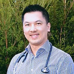 Dr Joanathan Tong smiling towards camera with medical stethoscope resting around his neck