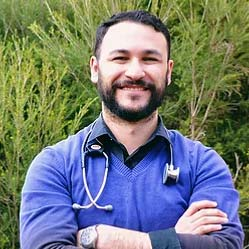 Dr Mostafa Khalafalla standing outside smiling with arms crossed and medical stethoscope resting around neck