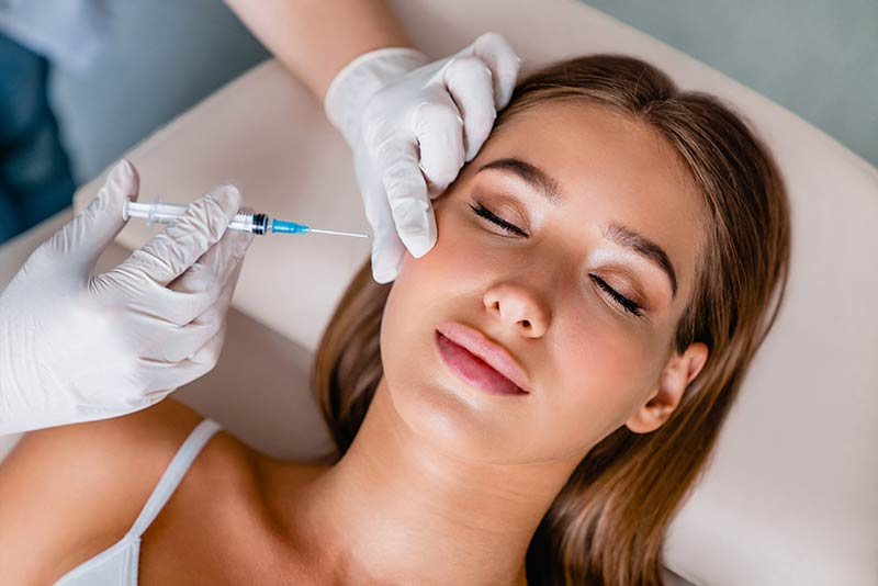 Woman at a cosmetic clinic receiving dermal fillers in her face.