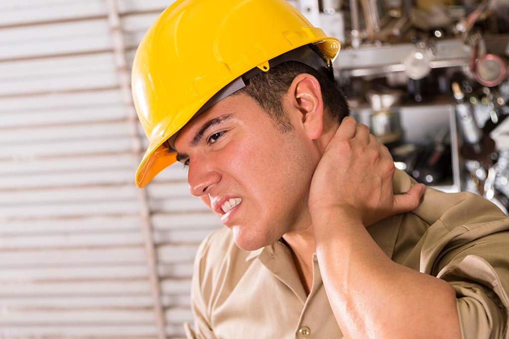 Man wearing hardhat feeling the back of his neck in pain as he awaits a medical examination